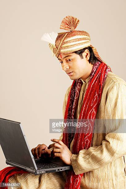 A bridegroom sitting with a laptop