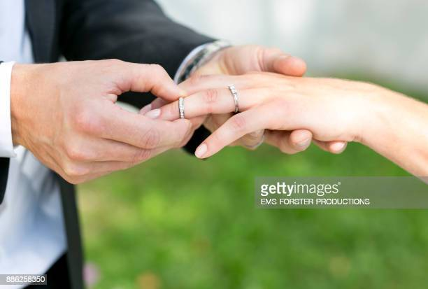 bridegroom slips wedding ring on brides ring finger