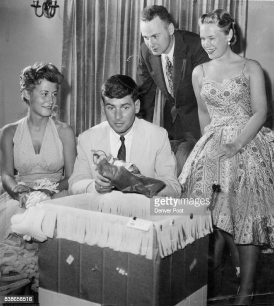 Bridegroom-to-be Russell Writer Jr. Opens gifts at the shower and cocktail party given for him on Wednesday eve. Onlookers are Miss Jan Fulscher, the...