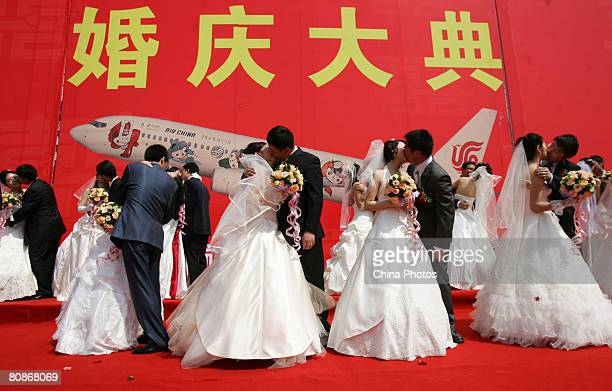 Brides and grooms from Air China kiss during their mass wedding April 26 2008 in Beijing China About 28 couples including pilots flight attendants...
