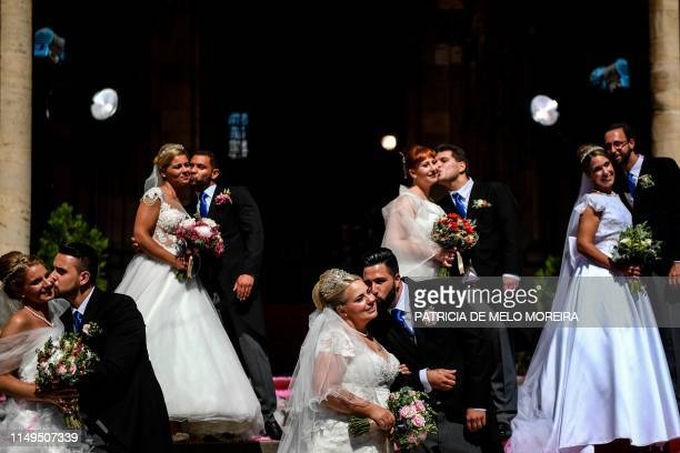 Brides and grooms kiss as they pose for a photo outside the Lisbon's Cathedral following their wedding ceremony in Lisbon on June 12, 2019. - It is...