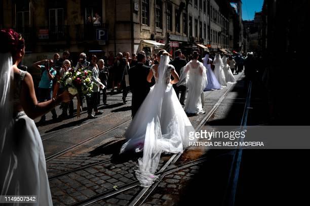 Brides and grooms parade along the streets of downtown Lisbon following their wedding ceremony at Lisbon's cathedral on June 12 2019 It is Lisbon's...