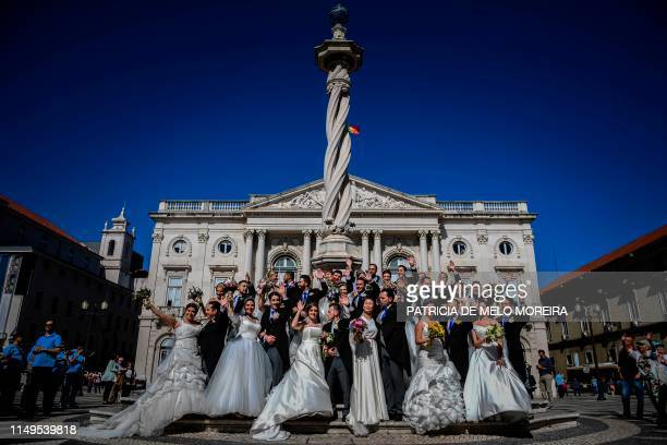 Brides and grooms pose after celebrating multiple wedding ceremonies at the city hall and the cathedral during Saint Anthony's day in Lisbon on June...