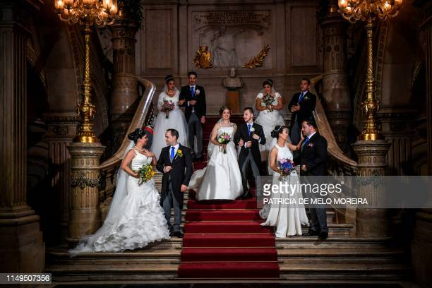 Brides and grooms pose for a photo following their civil ceremony at the Lisbon's city hall on June 12 2019 It is Lisbon's wedding of the year Crowds...