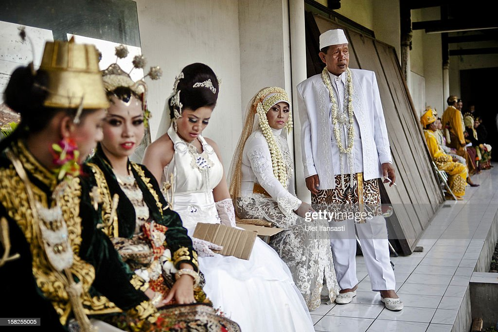 Brides and grooms prepare before their weddings as they get ready to take part in a mass Wedding ceremony on December 12, 2012 in Yogyakarta, Indonesia. Twelve couples participated in a mass wedding as today saw a surge in marriage across the globe to mark the once in a century date of 12/12/12.