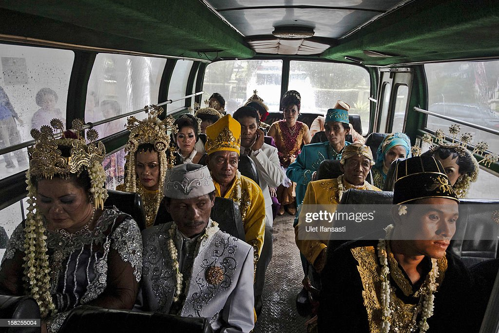 Brides and grooms sit on a bus before they get ready to take part in a mass Wedding ceremony on December 12, 2012 in Yogyakarta, Indonesia. Twelve couples participated in a mass wedding as today saw a surge in marriage across the globe to mark the once in a century date of 12/12/12.