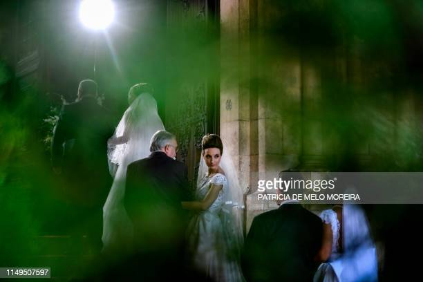 TOPSHOT Brides and their bestmen queue to enter the cathedral ahead of the celebration of a multiple wedding ceremony in Lisbon on June 12 2019 It is...