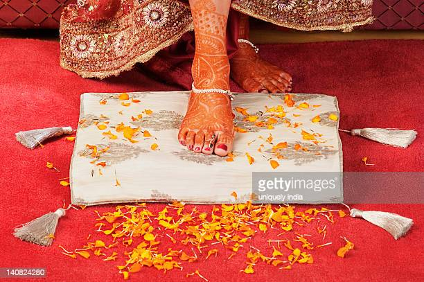 bride's foot on a cushion with flower petals - pretty asian feet stock photos and pictures