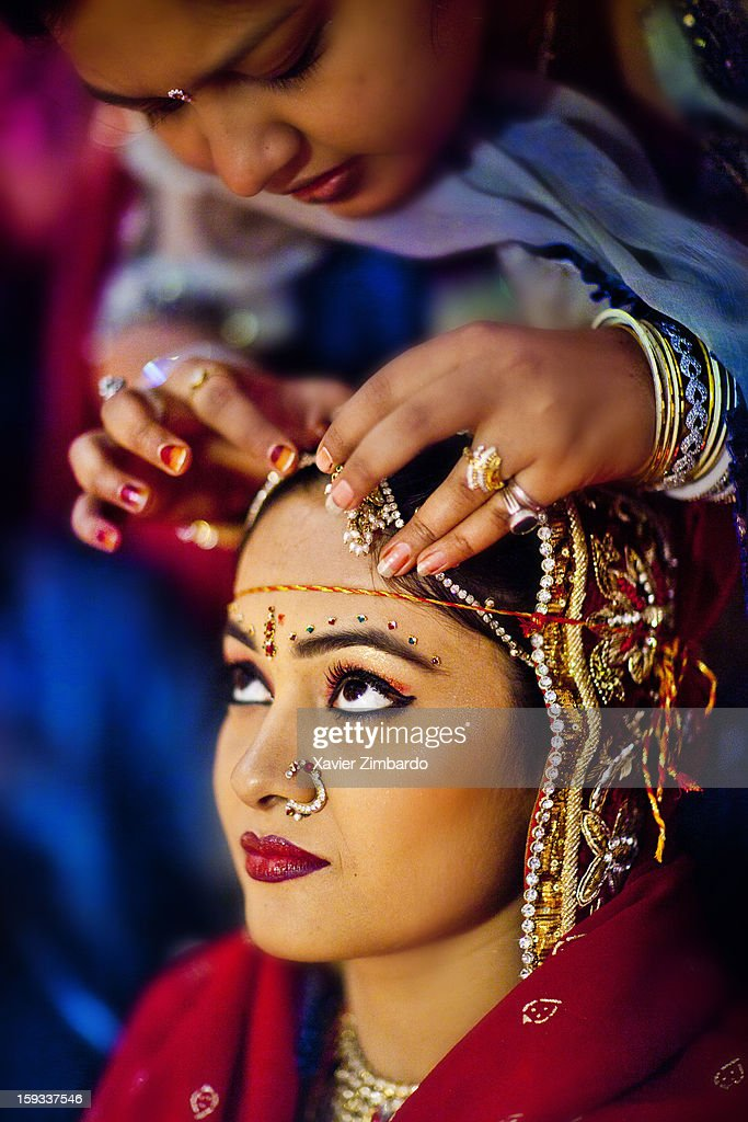 Bride's friend helping her by making some space to put 'sindoor' (holy red color) by the groom as per the wedding custom on January 4, 2012 at Khaas Bagh heritage hotel, in Jodhpur, Rajasthan, India.