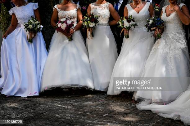 Brides hold their wedding bouquets following a multiple wedding ceremony at Lisbon's cathedral on June 12 2019 It is Lisbon's wedding of the year...