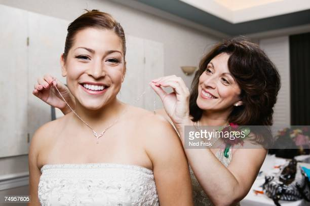 bride's mother putting necklace on daughter - indian bride stock photos and pictures