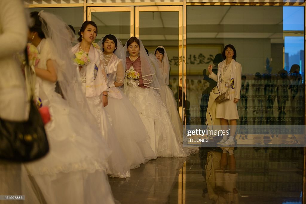 Brides queue to take photos prior to a mass wedding held by the Unification Church in Gapyeong on March 3, 2015. Hundreds of couples were married at the South Korean headquarters of the Unification Church --- the third such event since the death of church founder Sun Myung Moon.