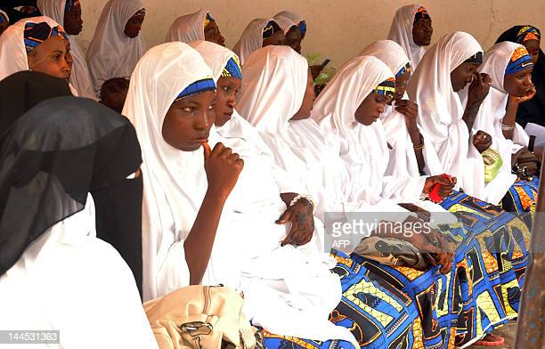 Brides sit on benches at the palace of the emir of Kano Ado Bayero near the central mosque in the northern Nigeria city of Kano on May 15 2012 for a...