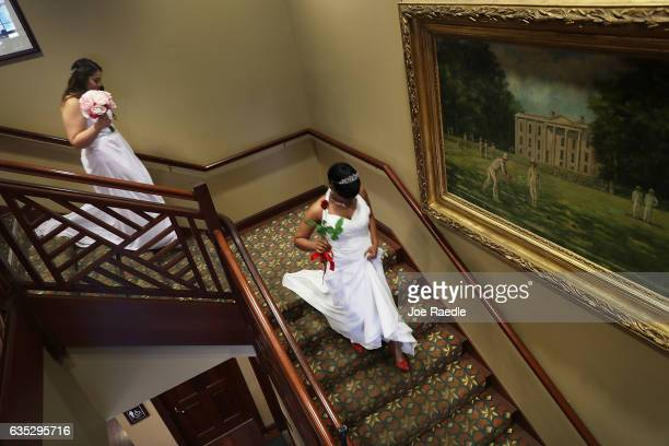 Brides walk down the stairs as they participate in a group Valentine's day wedding ceremony at the National Croquet Center on February 14 2017 in...