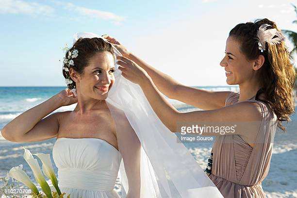 bridesmaid adjusting bride's veil - bridesmaid stock pictures, royalty-free photos & images