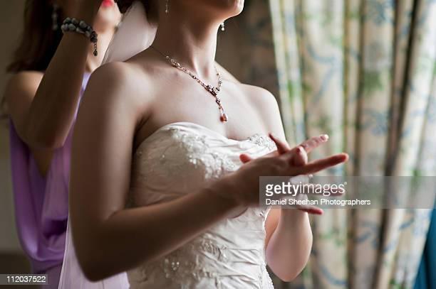 Bridesmaid adjusting bride's veil