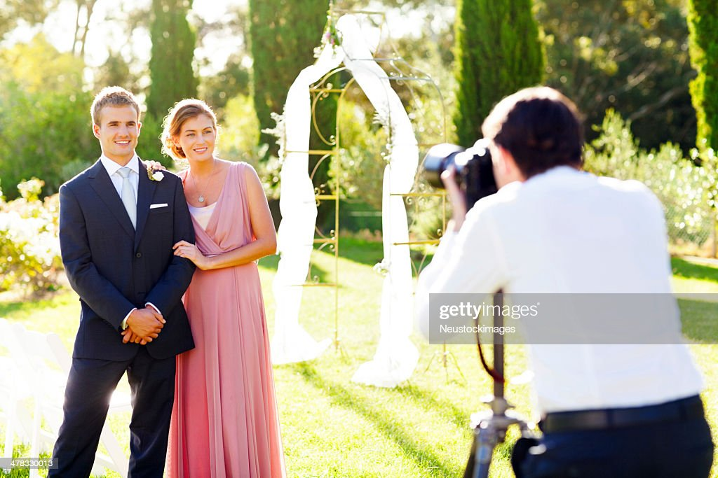 Bridesmaid And Best Man Posing For Photographer : Stock Photo