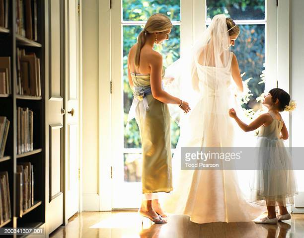 bridesmaid and flower girl (3-5) adjusting bride's veil, rear view - veil stock photos and pictures