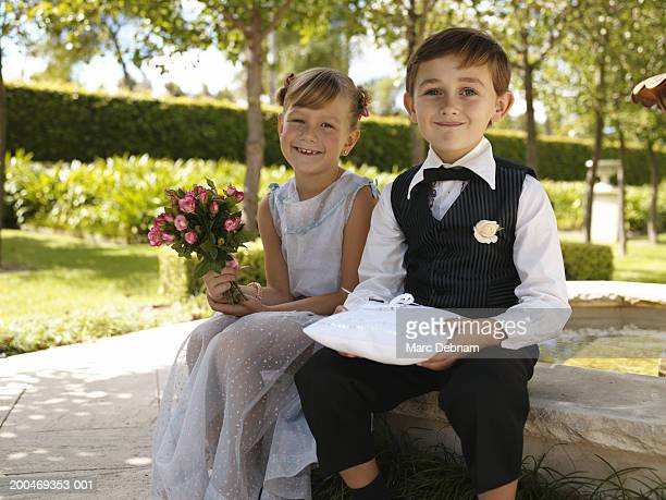 Bridesmaid and pageboy(6-7)sitting by fountain, smiling, portrait