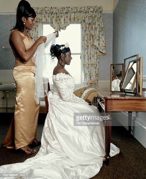bridesmaid attaching veil to seated bride in front of mirror - bridesmaid stock pictures, royalty-free photos & images