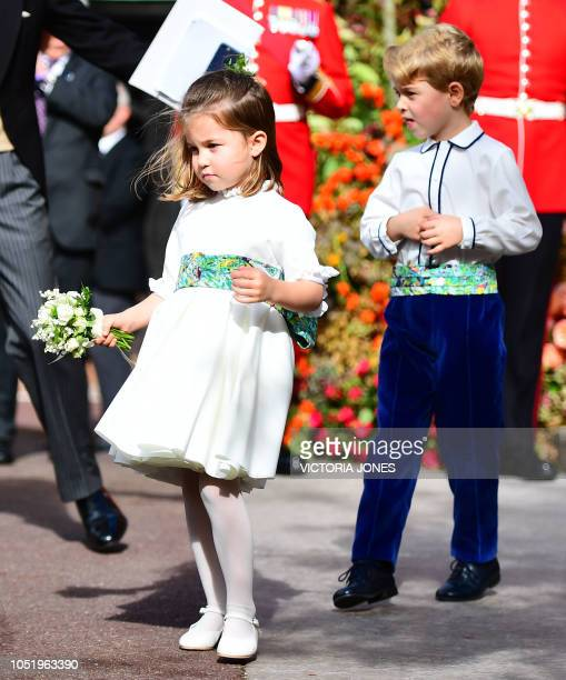 Bridesmaid Britain's Princess Charlotte of Cambridge and pageboy Prince George of Cambridge wave off Britain's Princess Eugenie of York and Jack...