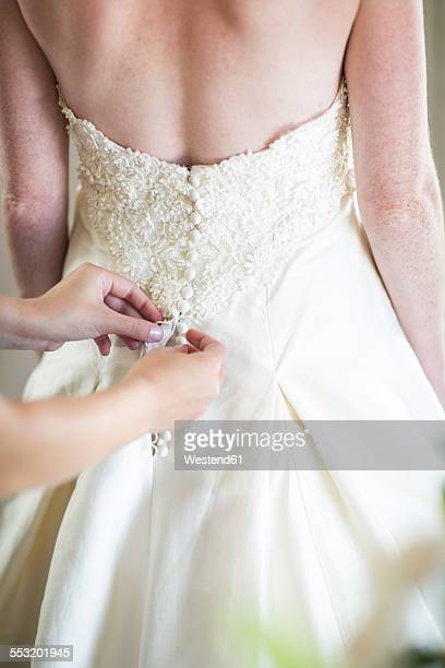 Bridesmaid buttoning up brides wedding dress