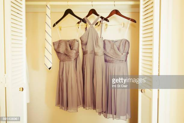 Bridesmaid dresses hanging in closet