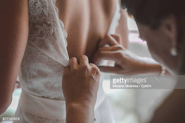 bridesmaid helping bride with dressing in bedroom during wedding - robe de mariée photos et images de collection