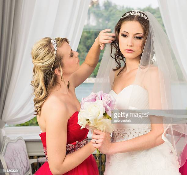 bridesmaid helping the bride to get ready - bridesmaid stock pictures, royalty-free photos & images