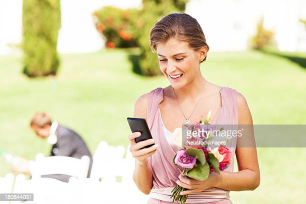 Bridesmaid Messaging Through Smart Phone At Garden Wedding