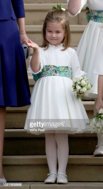 Bridesmaid Princess Charlotte of Cambridge waves as she stands on the steps after the wedding of Princess Eugenie of York and Jack Brooksbank at St...