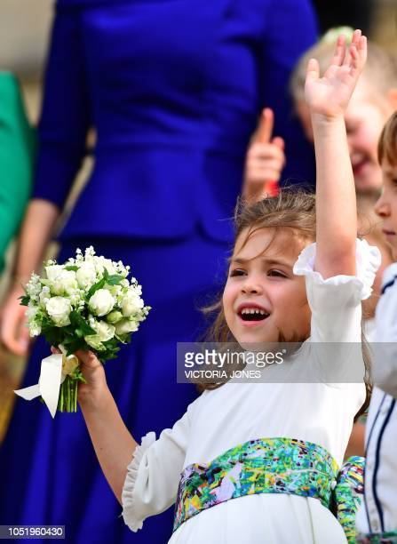 Bridesmaid Theodora Williams, daughter of Robbie Williams and Ayda Field, waves off Britain's Princess Eugenie of York and her husband Jack...