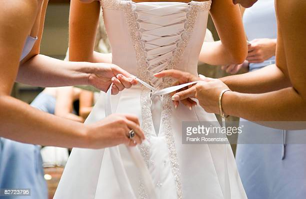 bridesmaids help bride into her dress - bridesmaid stock pictures, royalty-free photos & images
