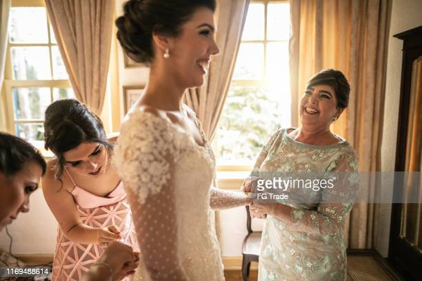 bridesmaids helping bride getting dressed for the wedding ceremony - bridesmaid stock pictures, royalty-free photos & images