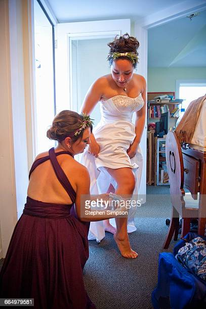 bridesmaids helping the bride get dressed