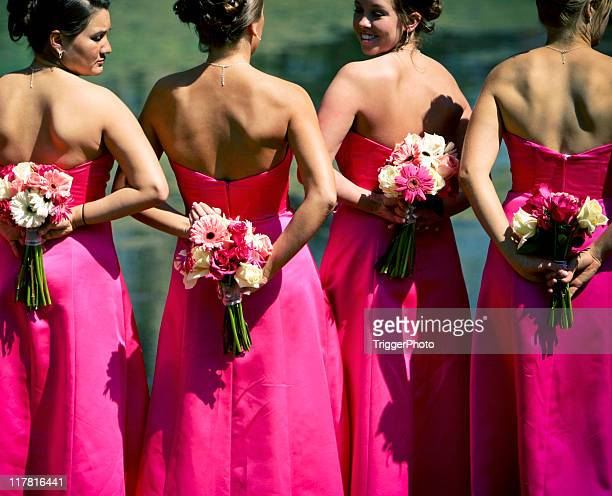 Bridesmaids in fuchsia pink gowns with flowers behind back