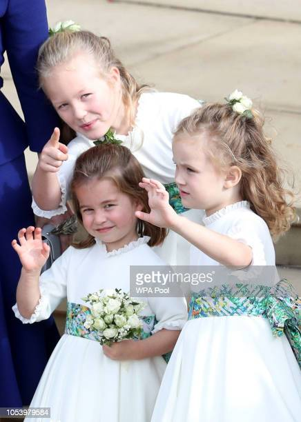 Bridesmaids Princess Charlotte of Cambridge, Savannah Phillips and Maud Windsor wave off Princess Eugenie of York and Mr. Jack Brooksbank following...