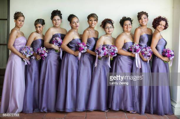 Bridesmaids with bouquets smiling in a row