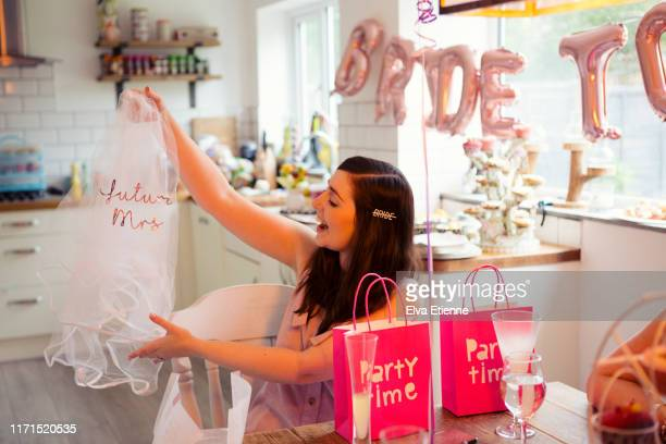 bride-to-be at a hen party holding up a novelty wedding veil - addio al nubilato foto e immagini stock