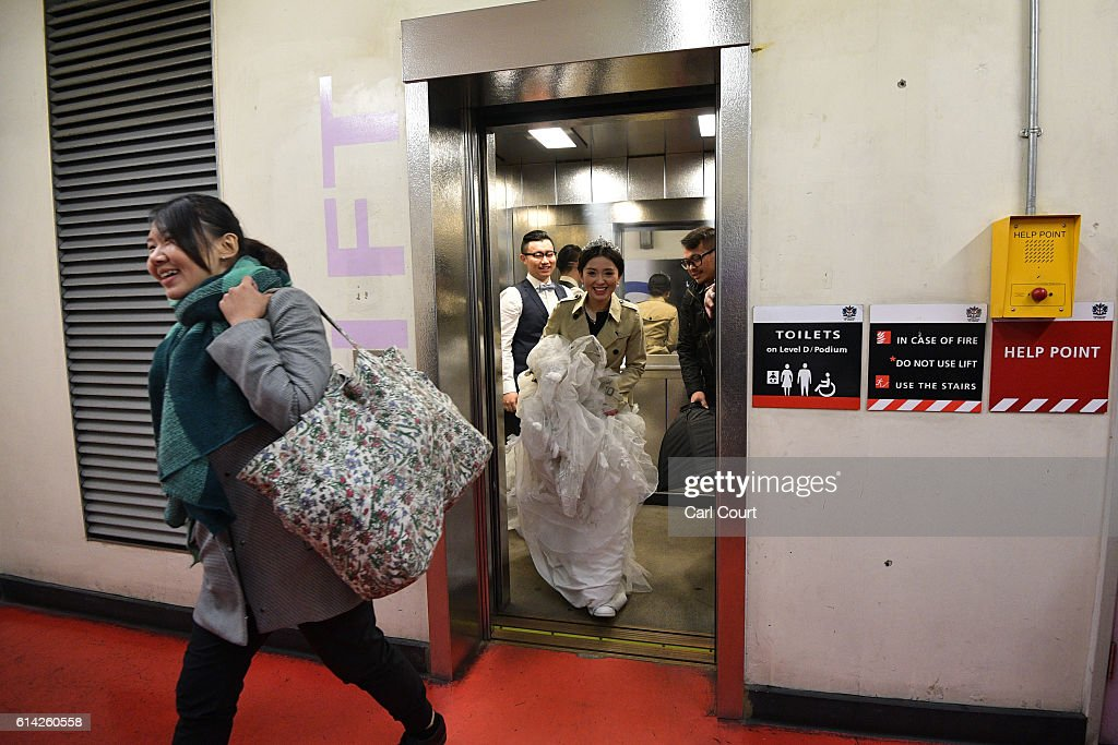 Bride-to-be Echo Li (C) exits a lift in a wedding dress as she makes her way to start a pre-wedding photography shoot at St Paul's Cathedral, on October 11, 2016 in London, England. It's a Chinese custom for couples to have their wedding photos taken before they are married and on the wedding day the photos will be shown to guests on cards and big screens. Photography studios such as J.R Studios in east London have seen business boom as the capital has become increasingly popular as a location for pre-wedding photography thanks in part to its instantly recognisable landmarks.