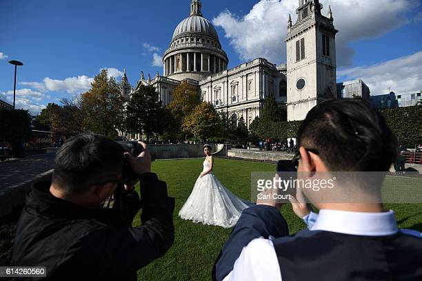 Bridetobe Echo Li has her photograph taken by photographer Dominic Wu and her fiance Charles Qian during a prewedding photography shoot at St Paul's...