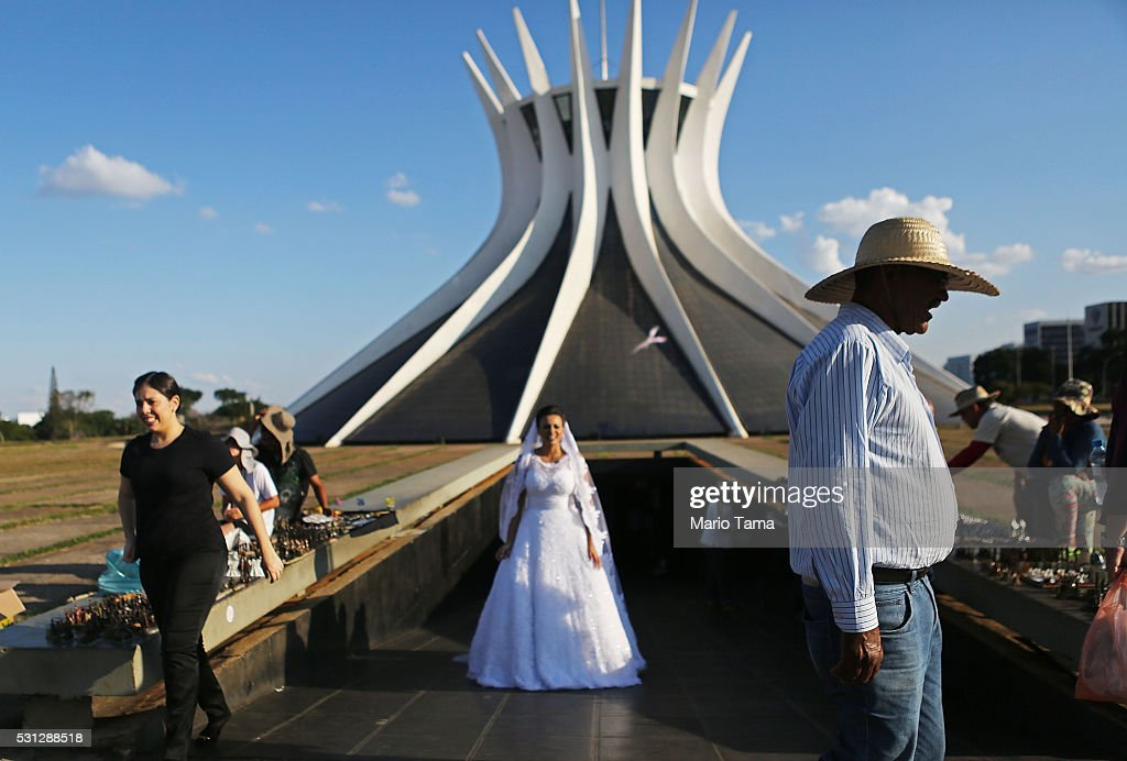 A bride-to-be poses while being photographed ahead of her wedding day outside the Cathedral of Brasilia a day after the Senate voted to accept impeachment charges against suspended President Dilma Rousseff on May 13, 2016 in Brasilia, Brazil. Brazil's interim President Michel Temer held his first offical meeting with new government ministers in the presidential palace today.