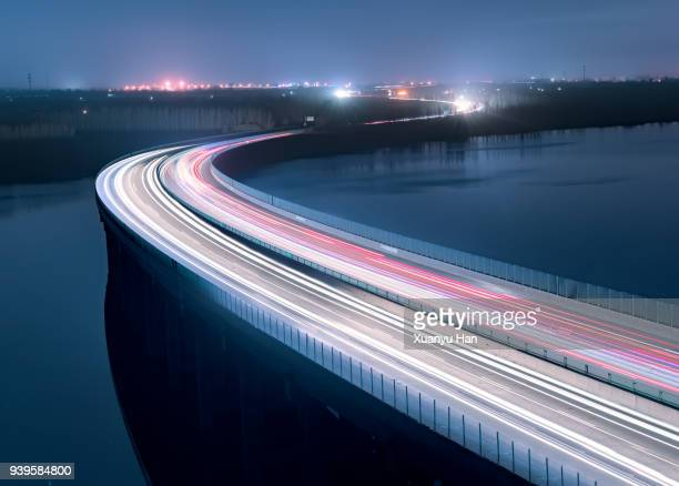 a bridge above a lake at night - verkehrswesen stock-fotos und bilder