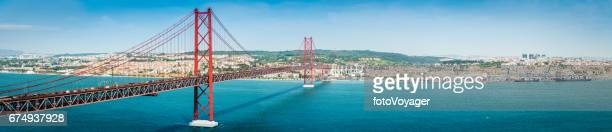 bridge across blue bay to city beyond lisbon panorama portugal - lisbon portugal stock pictures, royalty-free photos & images