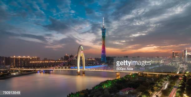 'Bridge across city river and Canton Tower at cloudy dusk, Guangzhou, Guangdong, China'