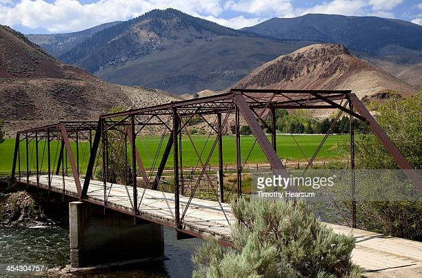 bridge across river to alfalfa field and ranch - timothy hearsum stock pictures, royalty-free photos & images