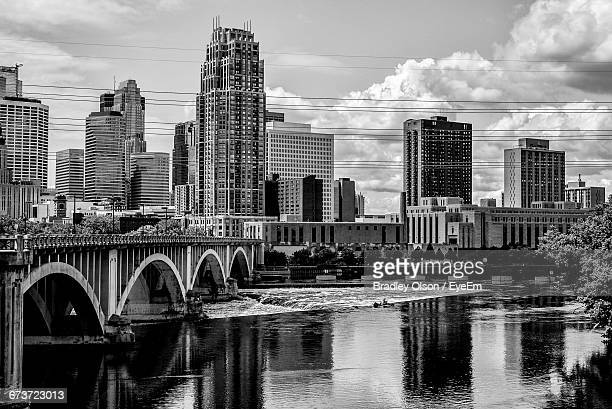 bridge and buildings by river against sky in city - minneapolis stock pictures, royalty-free photos & images