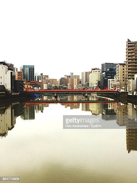 Bridge And Buildings Reflection In River Against Clear Sky