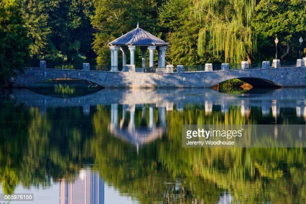 Bridge and gazebo reflecting in park river