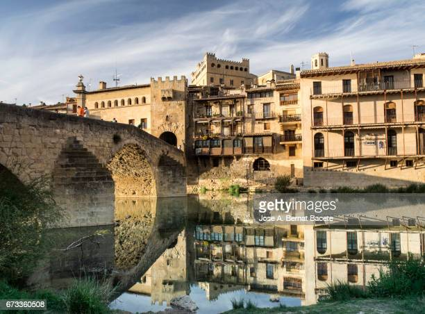 Bridge and medieval houses of entry to the people of Valderrobres, illuminated and reflected in the river to the late afternoon